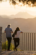 Tourists leaning on railing and looking at view at sunrise, Ronda, Andalusia, Spain