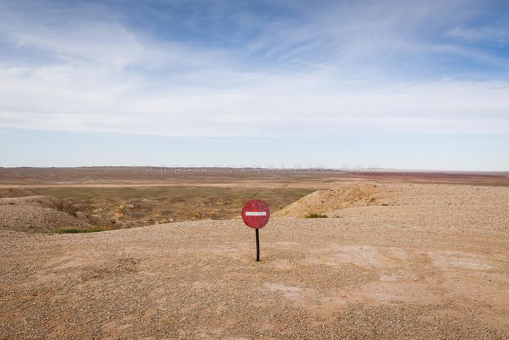 A stop sign marks the edge of the Tsagaan Suvraga cliffs in Dundgov Province, Mongolia. Photo © Robert van Sluis - www. robertvansluis.com