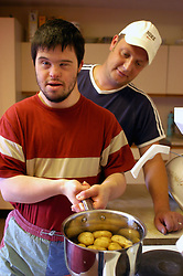 Young man with learning disability living in sheltered housing scheme; making his own meal with support worker in kitchen; UK