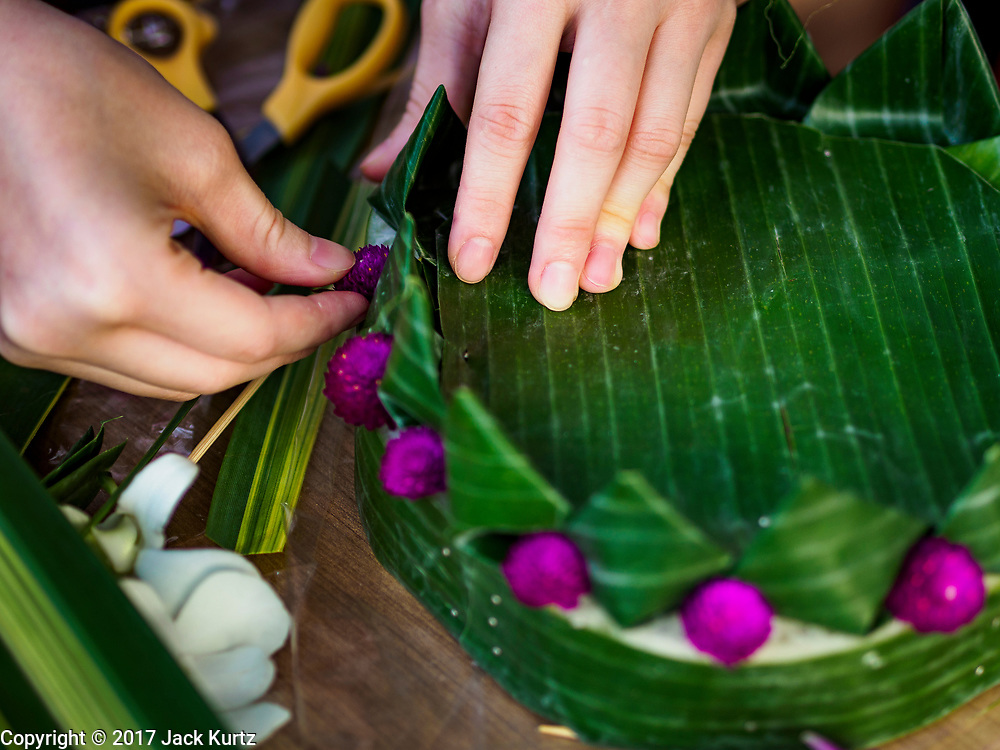 """03 NOVEMBER 2017 - BANGKOK, THAILAND: Young women make krathongs to float in the Chao Phraya River during Loi Krathong at Wat Prayurawongsawat on the Thonburi side of the Chao Phraya River. Loi Krathong is translated as """"to float (Loi) a basket (Krathong)"""", and comes from the tradition of making krathong or buoyant, decorated baskets, which are then floated on a river to make merit. On the night of the full moon of the 12th lunar month (usually November), Thais launch their krathong on a river, canal or a pond, making a wish as they do so. Loi Krathong is also celebrated in other Theravada Buddhist countries like Myanmar, where it is called the Tazaungdaing Festival, and Cambodia, where it is called Bon Om Tuk.     PHOTO BY JACK KURTZ"""