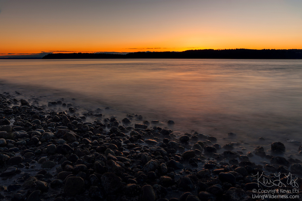 Puget Sound and the rocky beach at Mukilteo catch the last light of day as the sun sets behind Whidbey Island, Washington. A long exposure blurs the movement of the waves on Puget Sound.