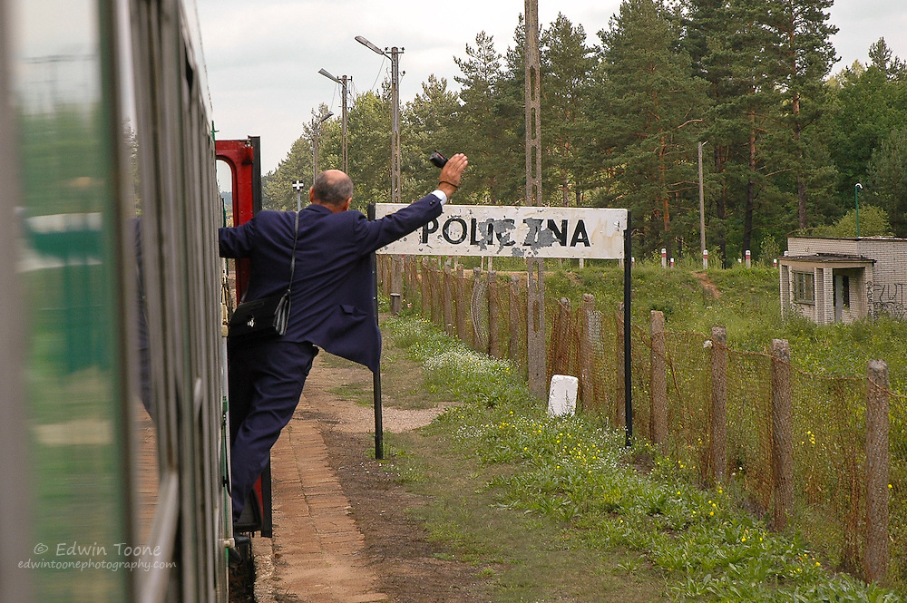 The ticket taker signals the conductor all aboard and ready to go in Policzna, Poland.