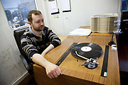 Vinyl factory worker manager checking and listening to vinyl test disks on specialist record player in sound proof booth. The Vinyl Factory is the old EMI vinyl works in Uxbridge, Middlesex, producing limited edition vinyls of new releases, plus re-presses of classics. They also act as a distributor of vinyl releases.