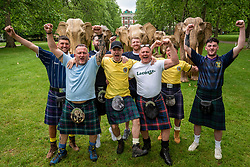 © Licensed to London News Pictures. 17/06/2021. LONDON, UK. Scotland football fans wearing traditional kilts pose with some of the 100 wooden elephants on display in Green Park, part of the CoExistence herd.  Handcrafted from a natural plant material called Lantana camara, the wooden elephants are currently on an installation tour of the UK to highlight a crowded planet and human encroachment on wild places. Scotland will play England in their Euro 2020 group game at Wembley Stadium the following day.  Photo credit: Stephen Chung/LNP