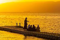 Jordanian women watching the sunset across the Gulf of Aqaba, Red Sea, Jordan from a dock at the Radisson Blu Tala Bay Resort.