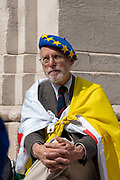 A man wearing a blue European Union beret, cloaked in a yellow flag, sitting outside Houses of Parliament on the first day after summer recess on 3rd September 2019 in London in the United Kingdom.