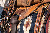 Brown western horse riding saddle with left stirrup up and cinch belt tightened, displaying red, navy and white patterned saddle blanket. Bit and reins are seen on the left.