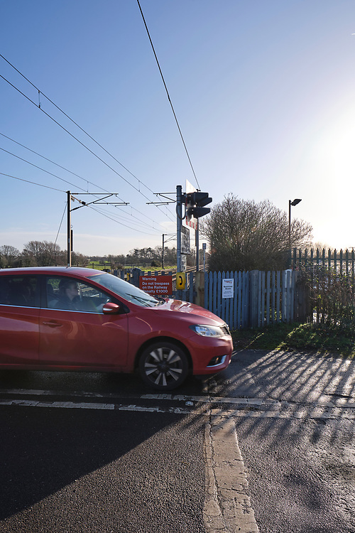 A car crosses a level crossing. Looking towards Ipswich on the Great Eastern Main Line in Baylham. Level crossing telephone & warning sign to not trespass.<br /> Photo by Jonathan J Fussell, COPYRIGHT 2020
