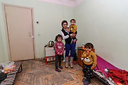 """A portrait picture of the Veronica's family standing in the living room on Tuesday, Dec 28, 2020. She said that they will not return to Nagorno Karabakh. They're now under Armenian government logistics support for food, shelter and other essential supplies. The family is living at an abandoned building of former """"SOVIET Hotel"""" in Metsamor, which is located near the Armenian Nuclear Power Plant, that is the only nuclear power plant in the South Caucasus, located 36 kilometres west of Yerevan in Armenia. (Photo/ Vudi Xhymshiti)"""