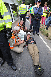 © Licensed to London News Pictures. 10/09/2013<br /> Anti Fracking protester has a bike padlock round his neck locked to a caravan in the middle of Balcombe Road B2036.<br /> Balcombe Camp Eviction.<br /> Anti- Fracking protesters have been warned to leave the camp site in Balcombe, West Sussex today (10.09.2013).<br /> Photo credit :Grant Falvey/LNP