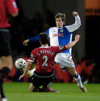 Photo: Jed Wee.<br /> Blackburn Rovers v Manchester United. Carling Cup. Semi Final, 1st Leg. 11/01/2006.<br /> <br /> Blackburn's Morten Gamst Pedersen (R) is tackled by Manchester United's Gary Neville.