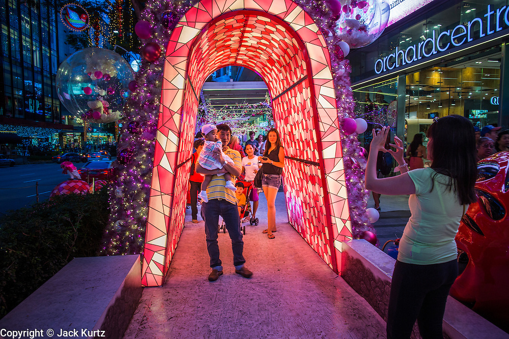 """22 DECEMBER 2012 - SINGAPORE, SINGAPORE:  People walk through Christmas decorations on Orchard Road in Singapore. Businesses on Orchard Road, Singapore's famed shopping street, sponsor """"Christmas on a Great Street"""" an annual event. The street is decorated with holiday lights, stores stay open late and crowds pack the area. This is the 8th year Singapore has held the """"Christmas on a Great Street"""" event.   PHOTO BY JACK KURTZ"""
