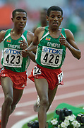 Haile Gebrselassie of Ethiopia leads countryman Kenenisa Bekele in the 10,000 meters in the IAAF World Championships in Athletics at Stade de France on Sunday, Aug, 24, 2003.