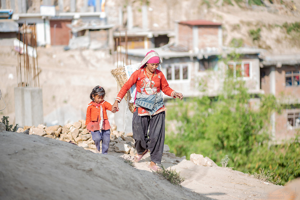 25 year-old Sapana Balami working as a labourer, carrying building materials, with her four year-old daughter, Aanchal Balami, Okharpauwa, Nuwakot District, Nepal