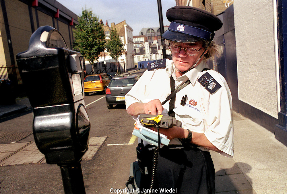 Traffic warden placing parking ticket on windscreen of car.