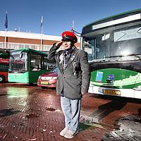 Nederland, Amsterdam , 6 februari 2013..Red Amsterdam organiseerde een demonstratie van diverse elektrische bussen op het voorplein bij de hoofdingang van het stadhuis.?Onder ruime belangstelling van de pers werden aan leden van de gemeenteraad en wethouder Eric Wiebes diverse elektrische bussen gepresenteerd en was er de mogelijkheid om een proefrit te maken..Volgens verkeerswethouder Eric Wiebes is de stand der techniek nog niet zover dat er binnenkort op grote schaal elektrische bussen kunnen worden ingezet. Bovendien zou het te kort dag zijn om een solide uitvraag naar elektrische bussen in de markt te zetten, waarmee in 2015 overgegaan zou kunnen worden op elektrisch rijden..Op de foto: een toevallige voorbijganger poseert spontaan voor de Chinese BYD electrische bus..Foto:Jean-Pierre Jans