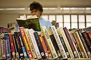 A prisoner chooses a book in the prison library. HMP Wandsworth, London, United Kingdom