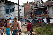 Young men guys on a rooftop with washing hanging and buildings in the background in Vila Valquiere, West Zone Zona Oueste, Rio de Janeiro