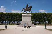 A dog walker passes beneath the bronze statue honouring French King Louis XIV who is depicted as a Roman Emperor, in Place du Peyrou on 17th June 2016, in Montpellier, France.