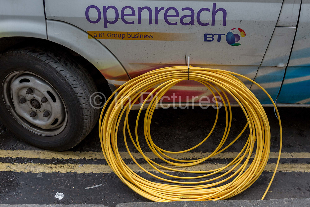 Detail of a BT Openreach van and a coil of yellow broadband fibre cable on the ground and awaiting installation, on 16th February 2017, in the City of London, England. Openreach is a subsidiary of telecommunications company BT Group that owns the pipes and telephone cables that connect nearly all businesses and homes in the United Kingdom to the national broadband and telephone network.