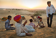 A family of camel herders watching the sun go down in the Thar Desert during the Jaisalmer Desert Festival on 21st February 2018  in Jaisalmer, Rajasthan, India. It is held in the Hindu month of Magh February, three days prior to the full moon.