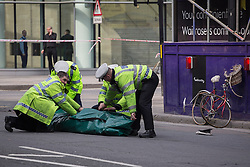 © licensed to London News Pictures. London, UK 08/04/2013.Police officers roll away a tent.  Police officers attending the scene where a woman cyclist killed in a rush hour collision on Victoria Street, London. Photo credit: Tolga Akmen/LNP