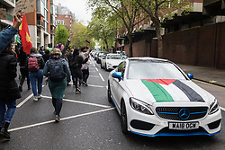 London, UK. 15th May, 2021. A vehicle draped with a Palestinian flag passes hundreds of people taking part in a Free Palestine SOS Colombia solidarity rally and march from the Colombian embassy to the Israeli Embassy. Speakers highlighted human rights abuses such as forced displacement being directed against Palestinians in Israel and the Occupied Territories and the killing, repression, detention and torture of peaceful demonstrators and human rights defenders in Colombia.