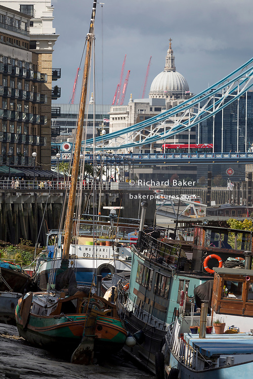 With the dome of St Paul's Cathedral the south suspension chains of Tower Bridge in the distance, privately-owned boats of many kinds sit in the low-tide mud on the Thames river at the a river community Tower Bridge Moorings, on 14th September 2017, in London, England.