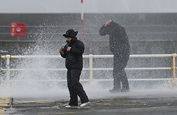 """© London News Pictures. 08/02/2014. Aberystwyth, UK. <br /> A couple get fought in a wave as gale force winds strike the sea walls at Aberystwyth, Wales at high tide. The winds are forecast to strengthen throughout the day, gusting up to 70 or 80 mph, and with the rising tide, their impact could be potentially damaging again. An amber """"be prepared"""" warning  has been issued by the Met Office for wind,. Photo credit: Keith Morris/LNP"""