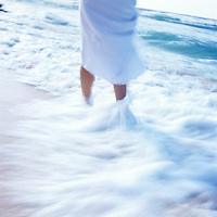 Female walking beach in wave shorebreak
