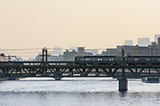 A commuter train cross a rail bridge above the Sumida River, Asakusa, Tokyo, Japan. Friday, February 4th 2011
