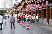 Uniformed Restaurant staff wait outside for customers. Chengdu, Kuan Zhai Xiang Zi historic city, Sichuan, China