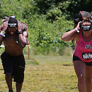 Competitors in action at the sand bag carry obstacle during the Reebok Spartan Race. Mohegan Sun, Uncasville, Connecticut, USA. 28th June 2014. Photo Tim Clayton