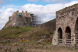 Lindisfarne Castle partially clad in scaffolding as it undergoes major restoration works, with the lime kilns in the foreground. Holy Island, Northumberland, England, UK<br /> Photo: Ed Maynard<br /> 07976 239803<br /> www.edmaynard.com