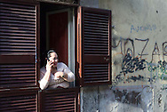 A woman talks on a cellphone as she stands in doorway window in Naples, Italy