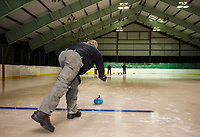 """Jim Bobotas throws a stone down to the """"house"""" for the awaiting """"sweepers"""" Margo Weeks, Dick Pease and Polly Doucet during the first night of Curling with Gilford Parks and Rec at the Arthur Tilton Ice Rink Thursday evening.   (Karen Bobotas/for the Laconia Daily Sun)"""