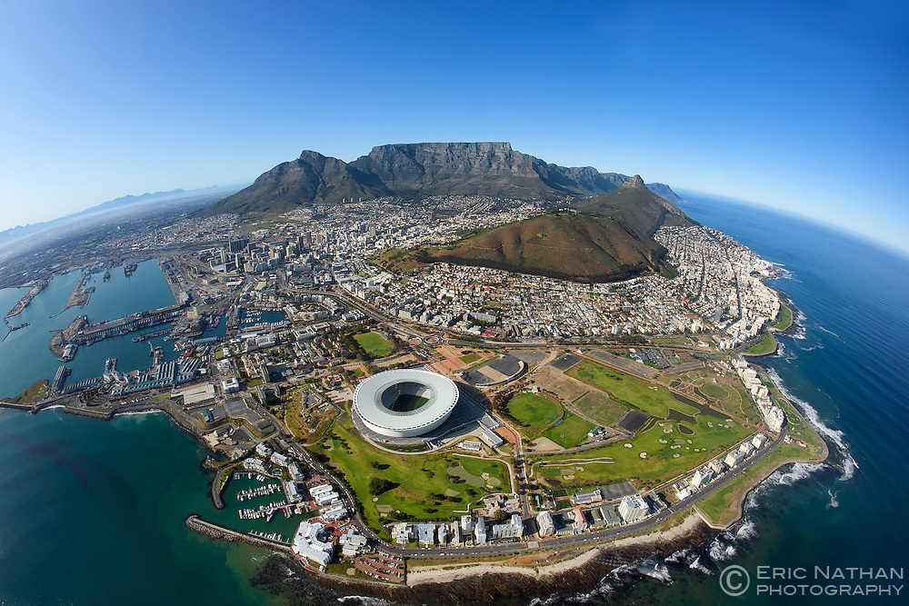 Aerial view of the city of Cape Town showing Table Mountain in the centre, Devil's Peak (left) and Lion's Head and Signal Hill (right). The Waterfront, Table Bay Harbour and Green Point stadium (used for the FIFA 2010 world cup) are visible in the foreground.