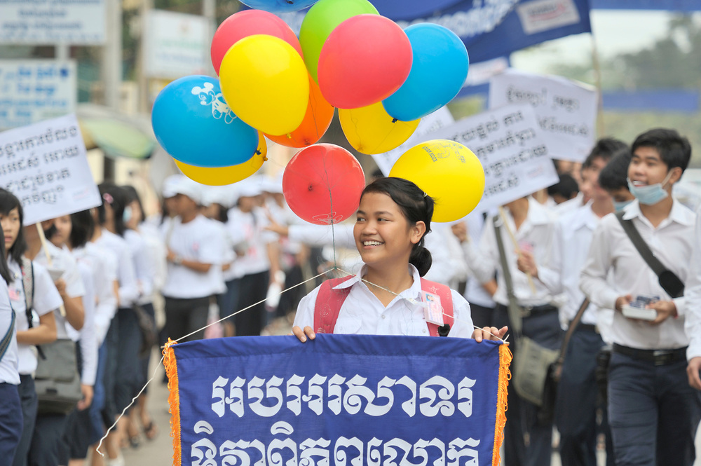Nith Nitikar, an 18-year old student, follows behind Buddhist monks to lead a march commemorating World AIDS Day in Battambang, Cambodia. Among sponsors of the march was the Salvation Centre Cambodia, an organization that works with Buddhist monks and other activists to foster support for people living with HIV and AIDS as well as public education and advocacy throughout the country.