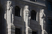 Mythical Greek male telamon figures look towards a female caryatid sculpture on the exterior of the Bank of England in the City of London.