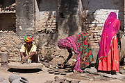 Potter in traditional Rajasthani turban works at home with his family making clay pots in Nimaj village, Rajasthan, India