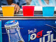 "09 AUGUST 2014 - BANGKOK, THAILAND:     Colored soft drinks for sale at the entrance to the Ruby Goddess Shrine in the Dusit section of Bangkok. The seventh month of the Chinese Lunar calendar is called ""Ghost Month"" during which ghosts and spirits, including those of the deceased ancestors, come out from the lower realm. It is common for Chinese people to make merit during the month by burning ""hell money"" and presenting food to the ghosts. At Chinese temples in Thailand, it is also customary to give food to the poorer people in the community.   PHOTO BY JACK KURTZ"