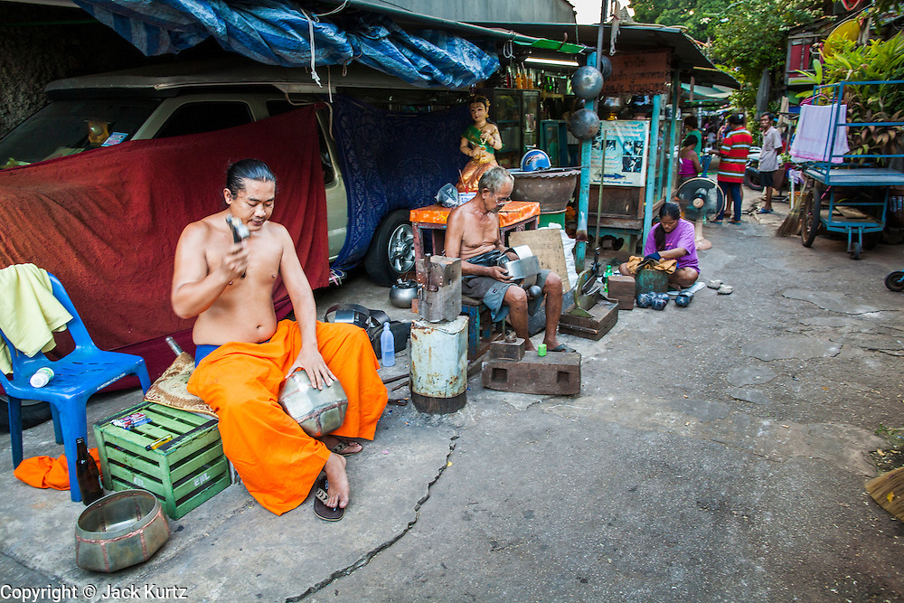 """03 DECEMBER 2012 - BANGKOK, THAILAND:  Bowl makers hand pound monks' bowls, called """"bat"""" (pronounced with a long """"a"""" as in baat) on Soi Baan Bat in Bangkok. The bowls are made from eight separate pieces of metal said to represent the Buddha's Eightfold Path. The Monk's Bowl Village on Soi Ban Baat in Bangkok is the only surviving one of what were originally three artisan's communities established by Thai King Rama I for the purpose of handcrafting """"baat"""" the ceremonial bowls used by monks as they collect their morning alms. Most monks now use cheaper factory made bowls and the old tradition is dying out. Only six or seven families on Soi Ban Baat still make the bowls by hand. Most of the bowls are now sold to tourists who find their way to hidden alleys in old Bangkok. The small family workshops are only a part of the """"Monk's Bowl Village."""" It is also a thriving residential community of narrow alleyways and sidewalks.  PHOTO BY JACK KURTZ"""