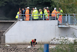 © Licensed to London News Pictures. 03/08/2019. Whaley Bridge, UK. THERESA VILLIERS , Secretary of State for Environment, Food and Rural Affairs , speaks to engineers on the dam at the edge of the reservoir . The town of Whaley Bridge in Derbyshire remains evacuated after heavy rain caused damage to a slipway on the Toddbrook Reservoir , threatening homes and businesses with flooding. Photo credit: Joel Goodman/LNP