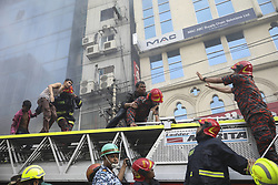 March 28, 2019 - Dhaka, Bangladesh - A Bangladeshi survivor reacts after being rescued by firefighters from a burning office building in Dhaka on March 28, 2019. A fire in a high-rise office building in Dhaka killed twenty five people. (Credit Image: © Ahmed Salahuddin/NurPhoto via ZUMA Press)