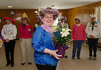 "Claire Lebel receives an Easter Lily for her ""Birds Nest"" Bonnet during Laconia Elders Friendship Club's annual Easter parade Wednesday afternoon at the Leavitt Park Clubhouse.  (Karen Bobotas/for the Laconia Daily Sun)"