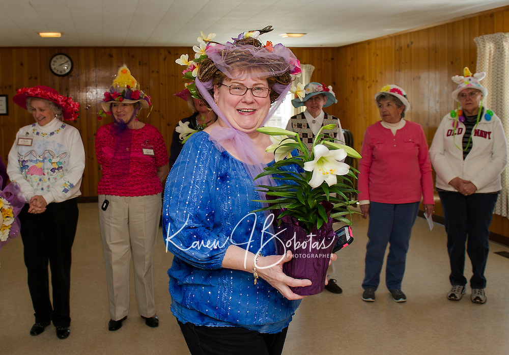 """Claire Lebel receives an Easter Lily for her """"Birds Nest"""" Bonnet during Laconia Elders Friendship Club's annual Easter parade Wednesday afternoon at the Leavitt Park Clubhouse.  (Karen Bobotas/for the Laconia Daily Sun)"""
