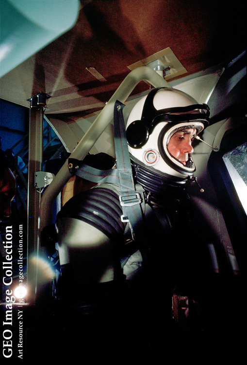 Space-suited test subject works in a flight simulator.