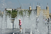 © Licensed to London News Pictures. 31/05/2013. London, UK A young girl plays in the fountains with the Tower of London in the background. Children and office workers enjoy the hot weather near to City Hall and Tower Bridge in London today May 31st 2013. Photo credit : Stephen Simpson/LNP