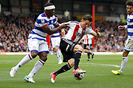 Brentford forward Lasse Vibe (21) holds of Queens Park Rangers defender Nedum Onuoha (5) during the EFL Sky Bet Championship match between Brentford and Queens Park Rangers at Griffin Park, London, England on 22 April 2017. Photo by Andy Walter.