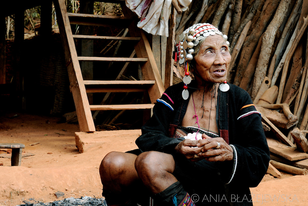 Burma/Myanmar, nearby Kentung. Elderly woman from Akha hilltribe sitting near her house.